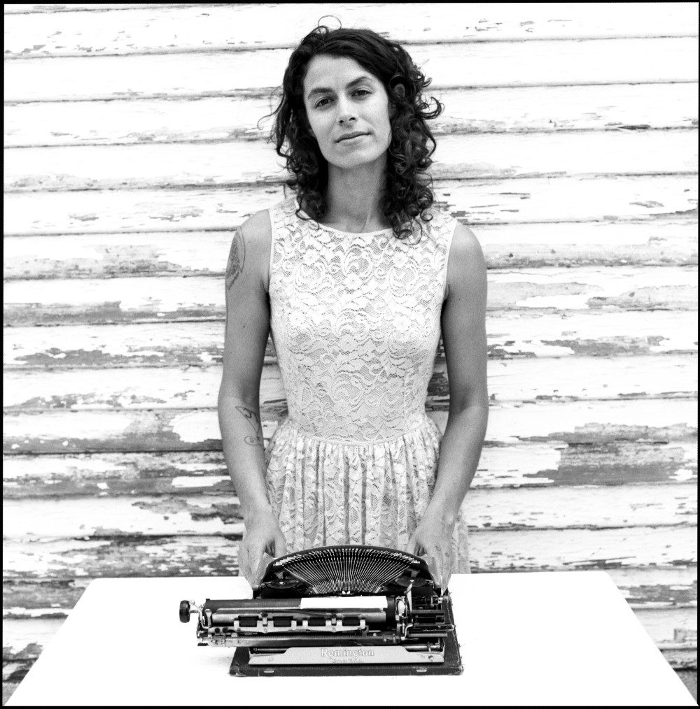 black and white photo of Jacqueline Suskin standing behind her cool old-school typewriter