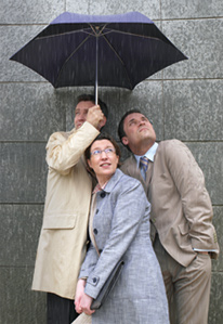 Photo of three people standing beneath one umbrella