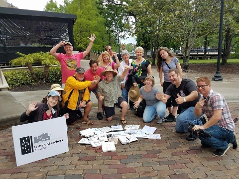 Group photo from an urban sketching workshop, with sketchers huddled around sketches laid together on the floor