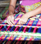A woman weaving bright pink & blue fabric