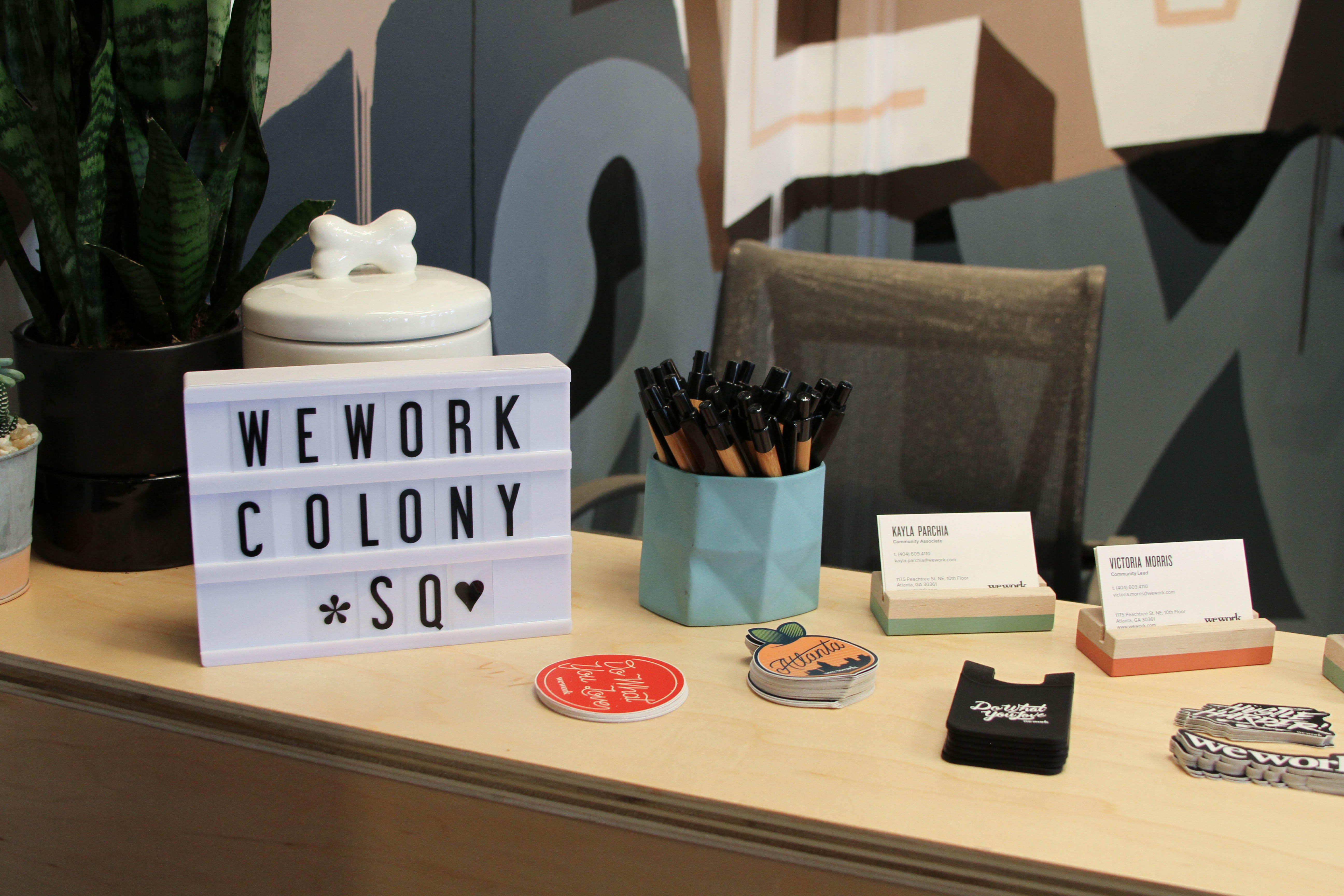 Picture of information desk at WeWork Colony Square. On the desk, there is a light up marquee sign that says WeWork Colony *Sq with a heart.  Near the Marquee sign are various WeWork stickers including a peach, a sticker that says