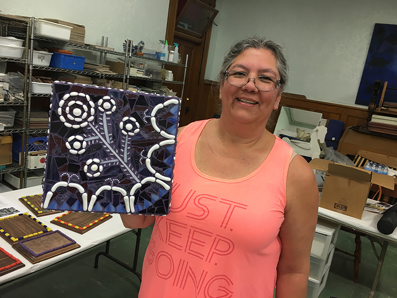mosaic class participant with her finished piece