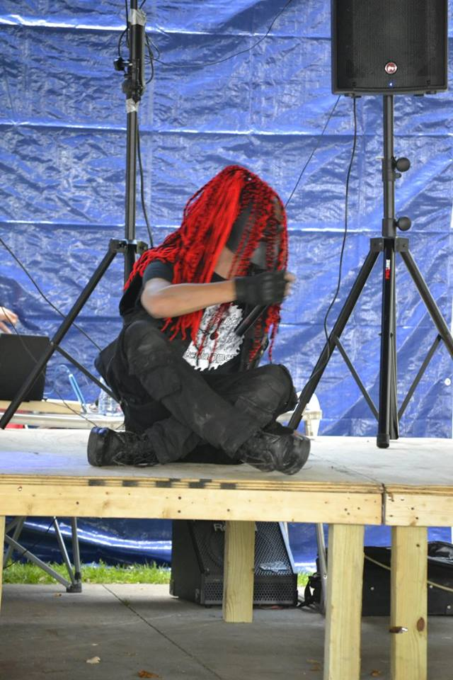 DJ Brutal in black attire withPredator stle mask and red fiber locs attached. seated on stage.