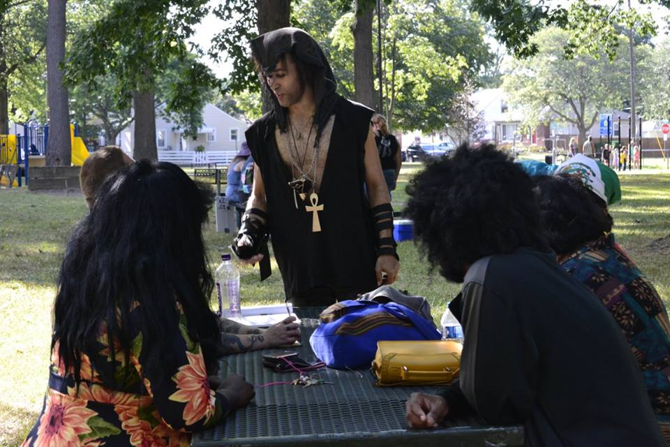 Male instructor dressed in ritual garb with Kemetic jewelry instructs class in Heka. Surrounding him, are students of various genders and ages. Setting is outside at venue picnic area.