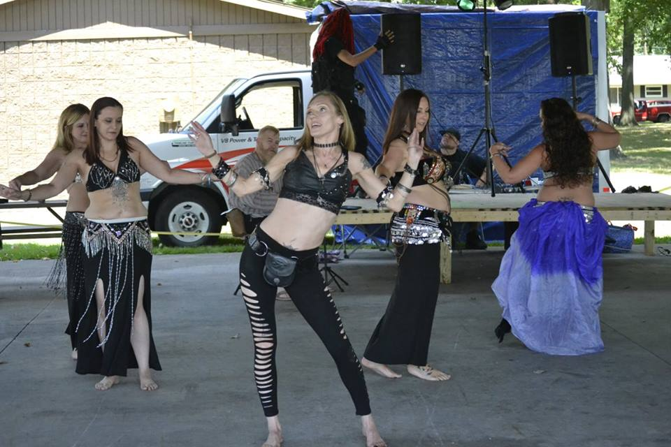 Magic in Motion belly dance troupe, women in black performing oriental dance.