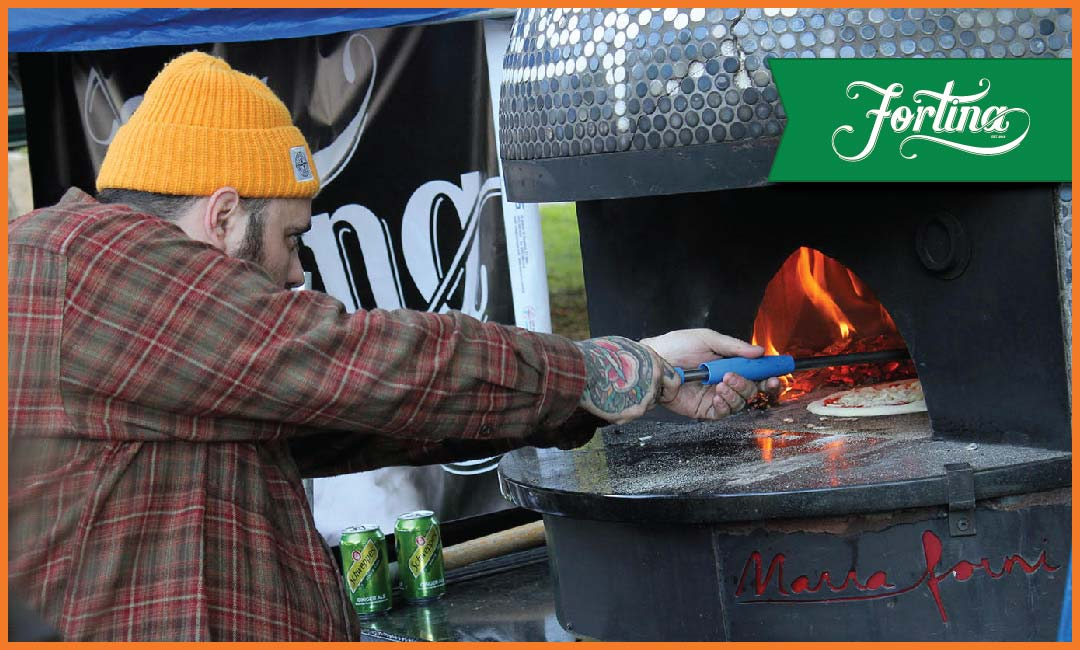 Man in hat taking pizza out of a mobile oven