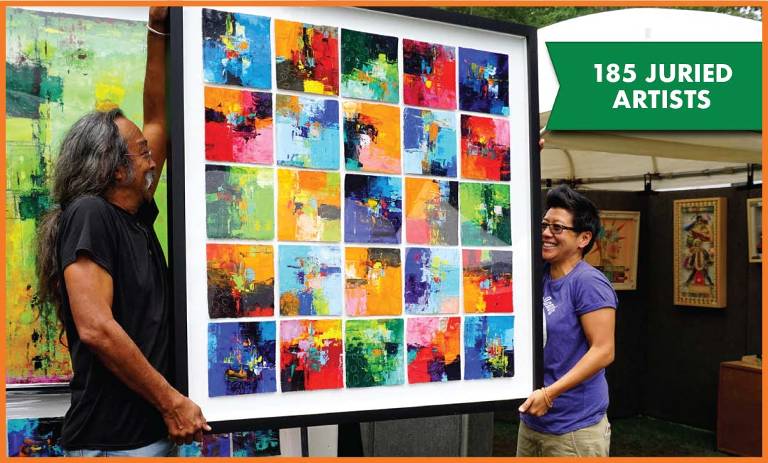 two people holding a colorful, large piece of artwork