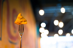 Samosa on a fork in front of colours and fairy lights
