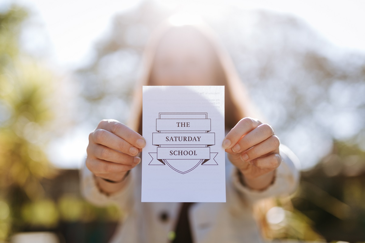 staff member holding up The Saturday School flyer