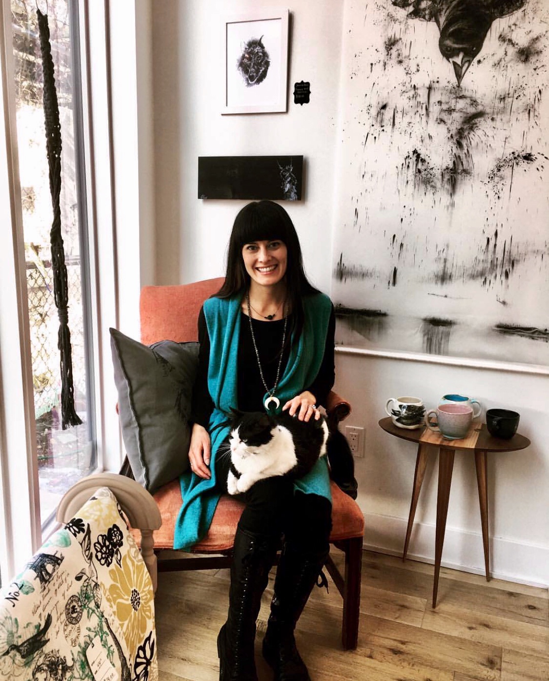 picture of artist sitting in chair in front of her silkscreen print
