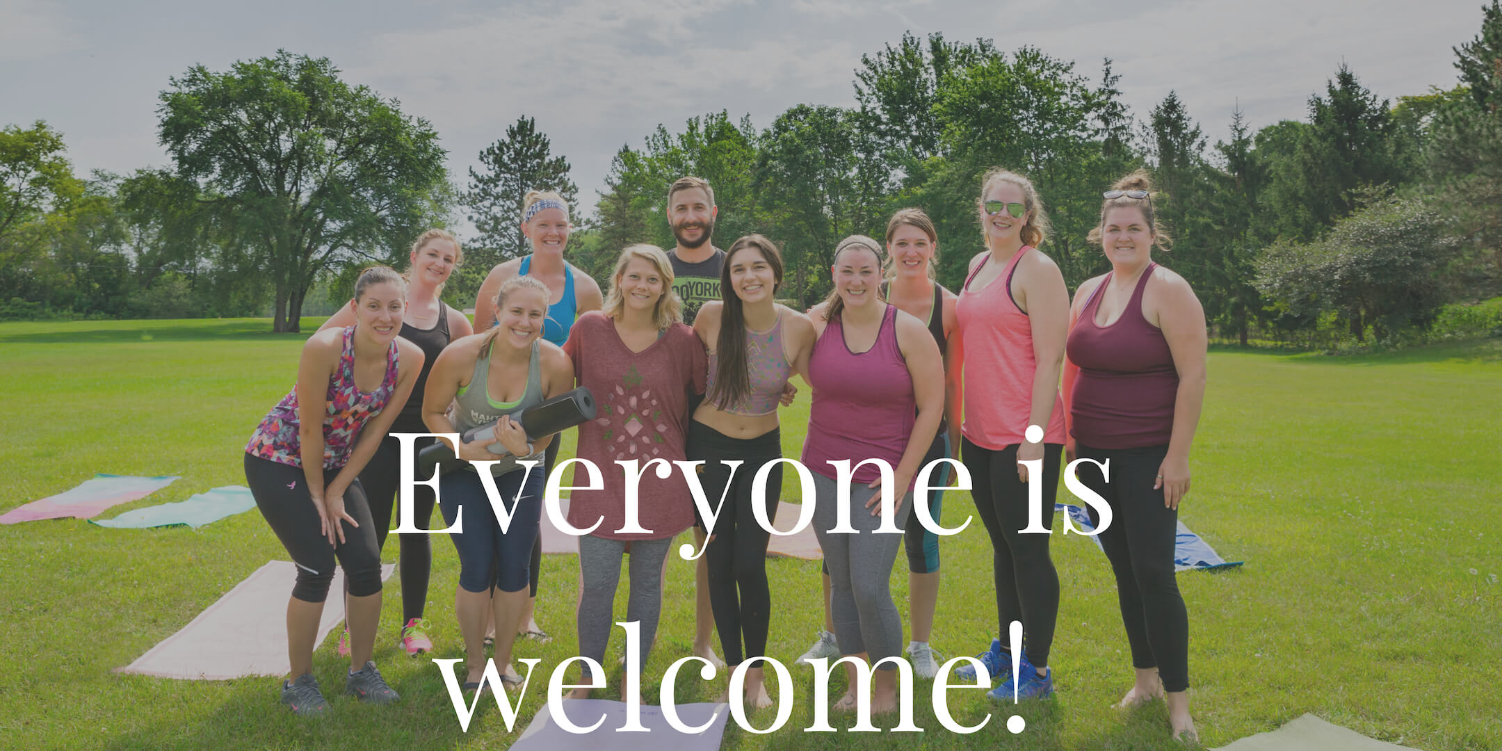 Image is of a group of yogis standing together outside.