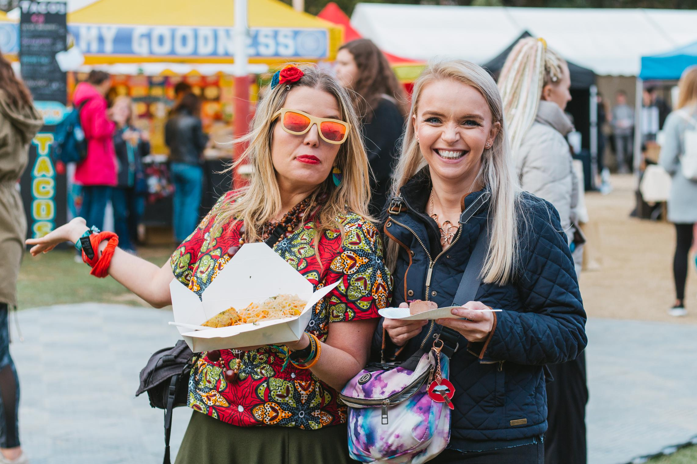 A WOMAN WEARING MIRROR SUNGLASSES INA COLOURFUL OUTFIT HOLDING VEGAN FOOD WITH ANOTHER WOMAN ALSO HOLDING FOOD SMILING AND LAUGHING AT DUBLIN VEGFEST