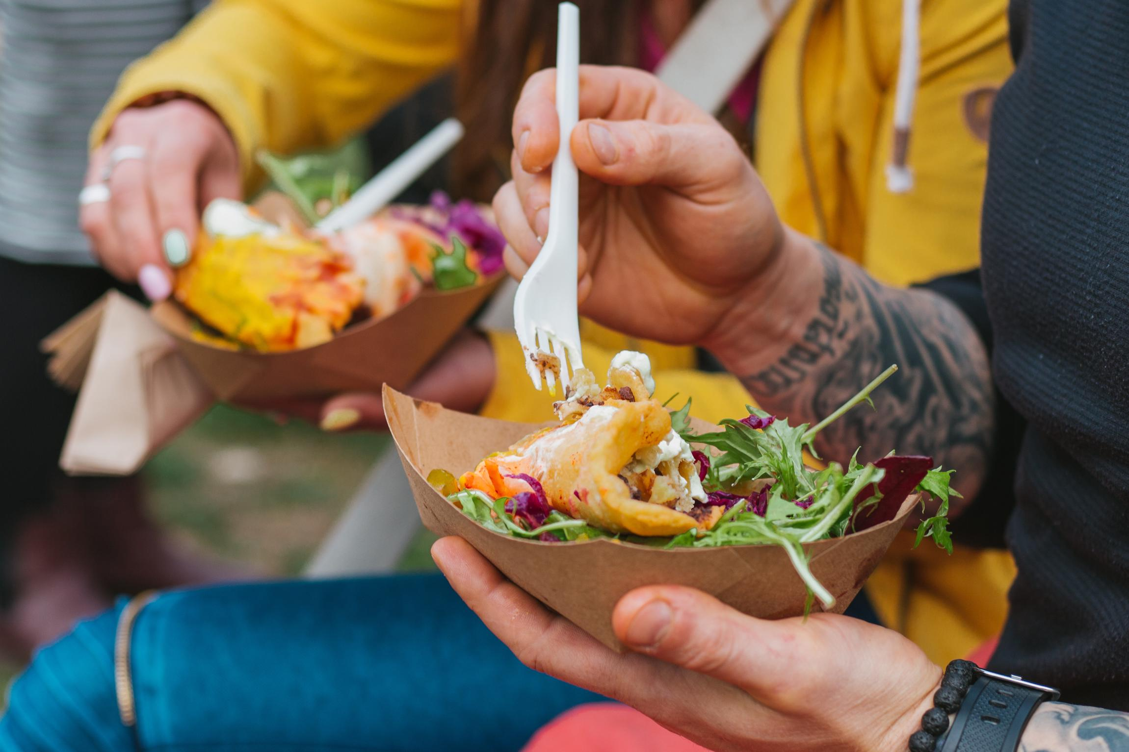 HANDS HOLDING FORKS IN PAPER BOAST FULL OF VEGAN TACOS AND SALAD. AT VEGFEST.