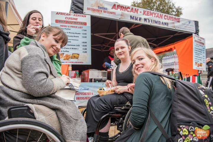 MIXED GROUP OF WOMEN SMILE IN VEGAN FOOD VILLAGE AT DUBLIN VEGFEST. SOME ARE WHEEL CHAIR USERS. AFRICAN CUISINE FOOD VENDOR IN BACKGROUND.