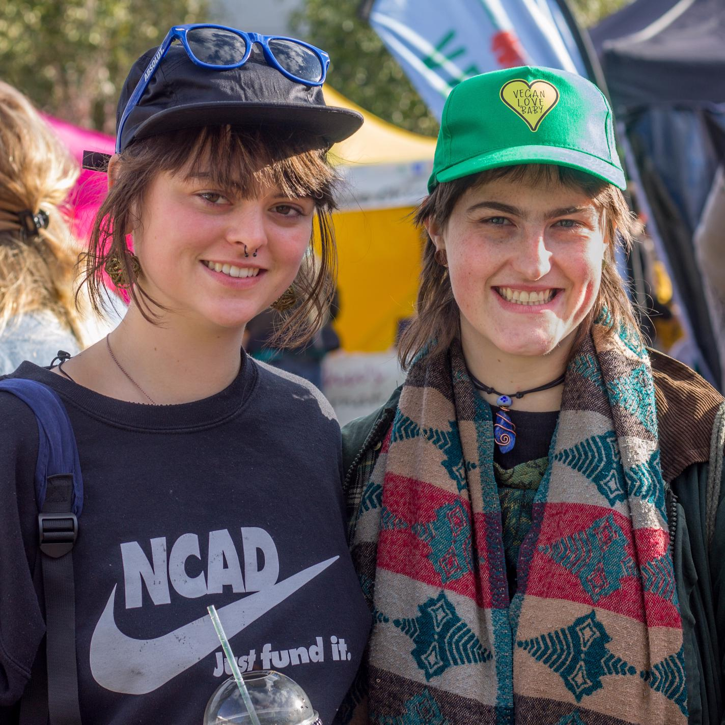 TWO YOUNG WOMEN SMILING. WEARING TRUCKER/BASEBALL CAPS