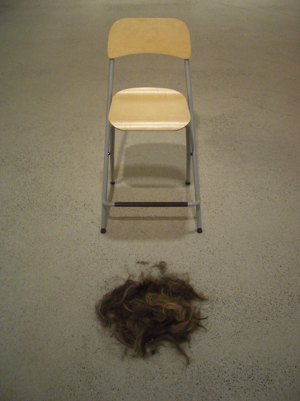 Image of seat with cut hair on floor in front