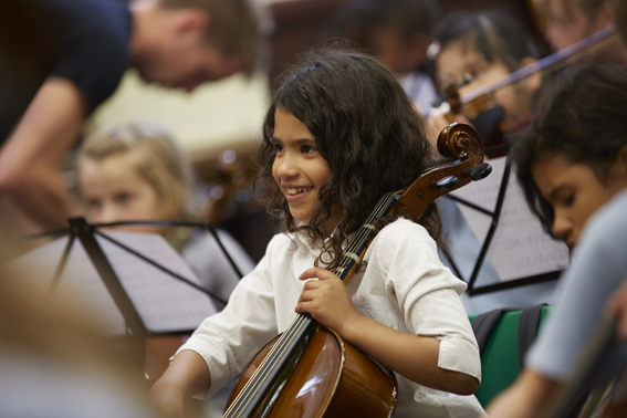 girl playing cello with big smile