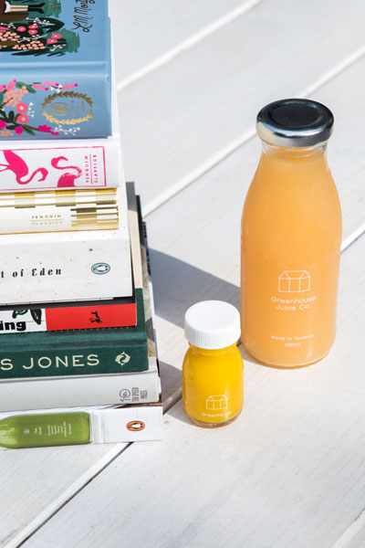 Greehouse Juice Co. juices next to a pile of books