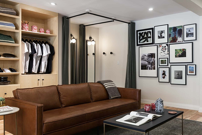 The Kotn living room with a brown leather couch and light wood shelving with their products behind, next to a fitting room.