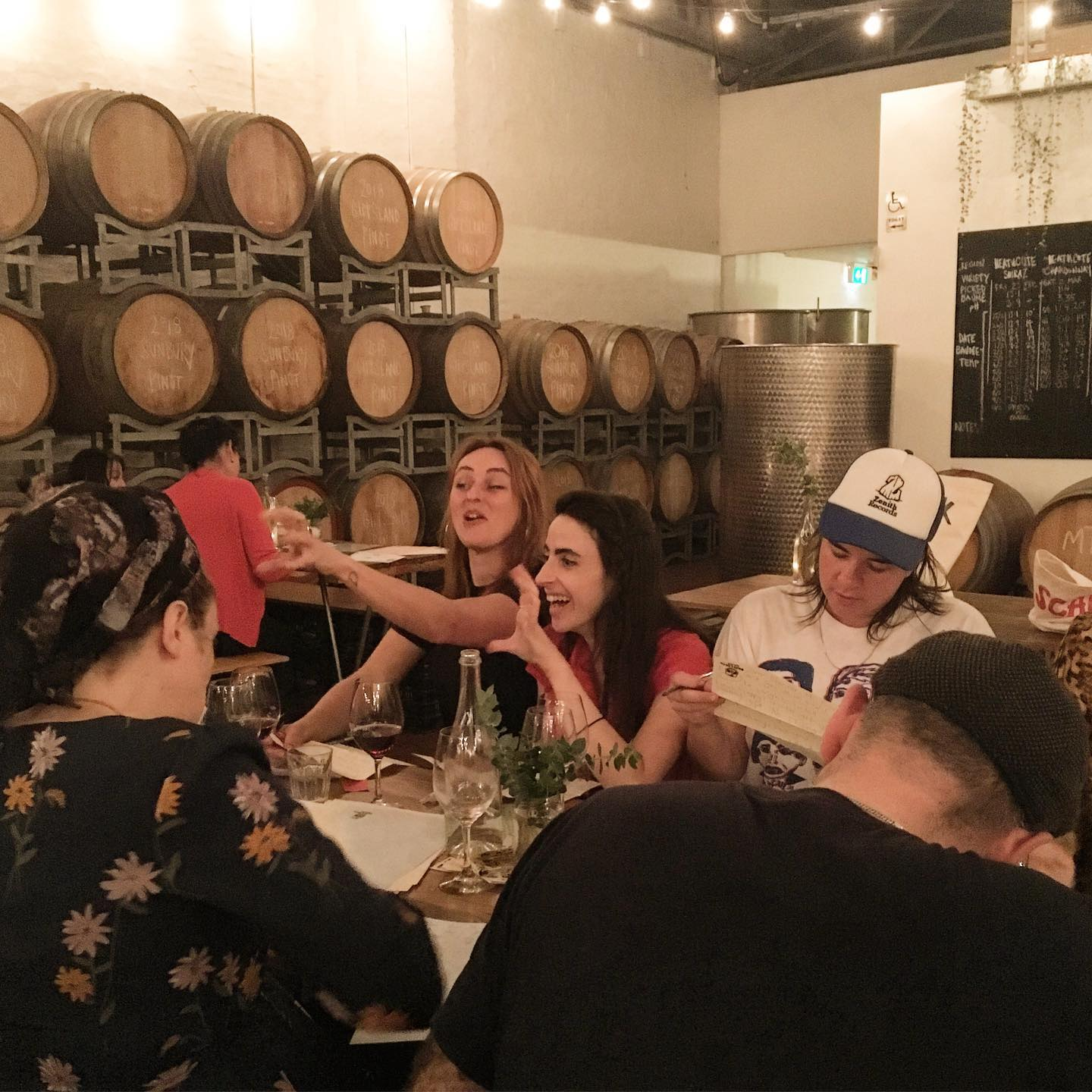 People laughing and sharing food and wine while writing at the Dead Letter Club event