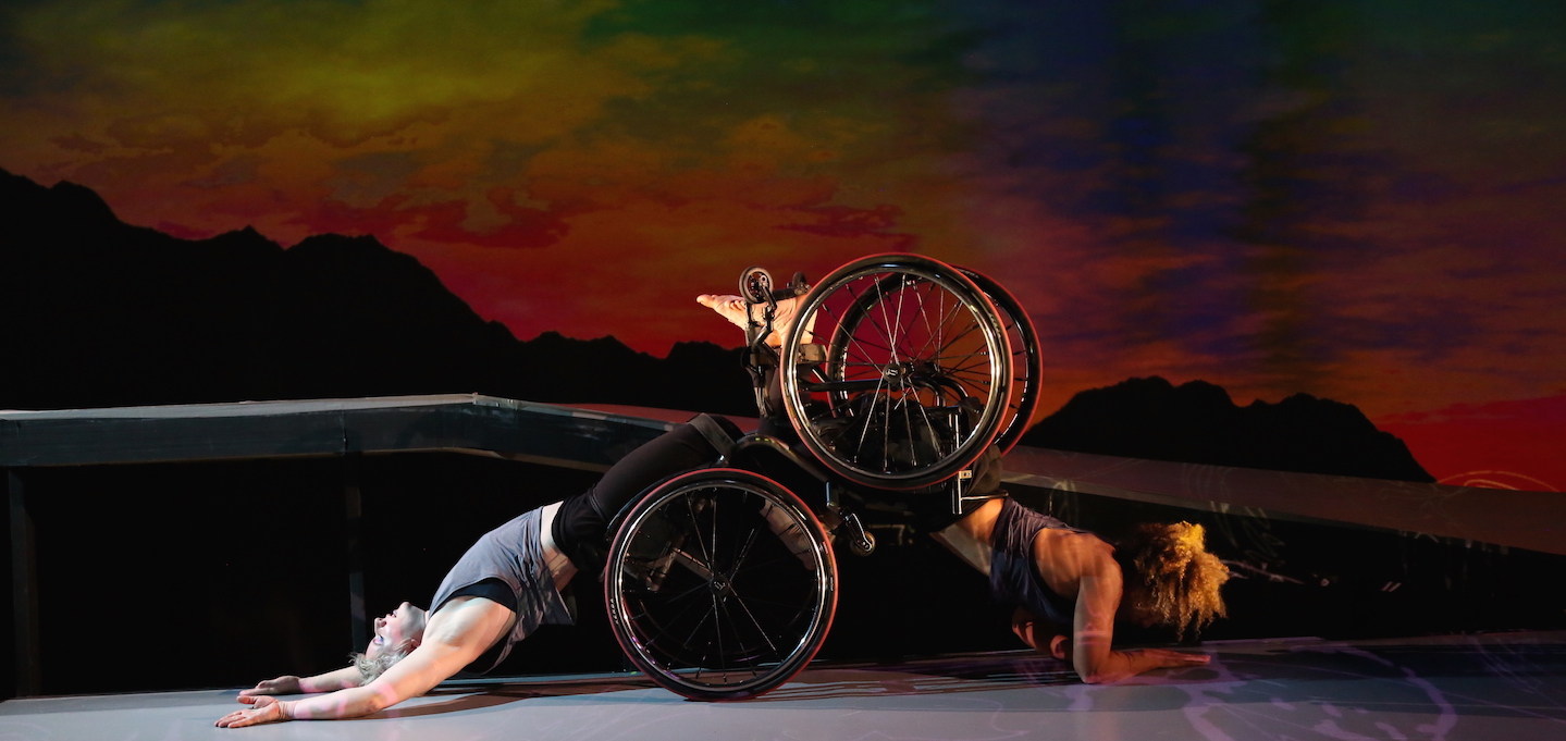 Andromeda and Venus both in their wheelchairs with a vibrant sunset in the background. Andromeda is crawling on her forearms with her knees in Venus' footplate, and Venus is arching her back on the ground as she is dragged along the floor. Andromeda is exerting effort, and Venus is in surrender.