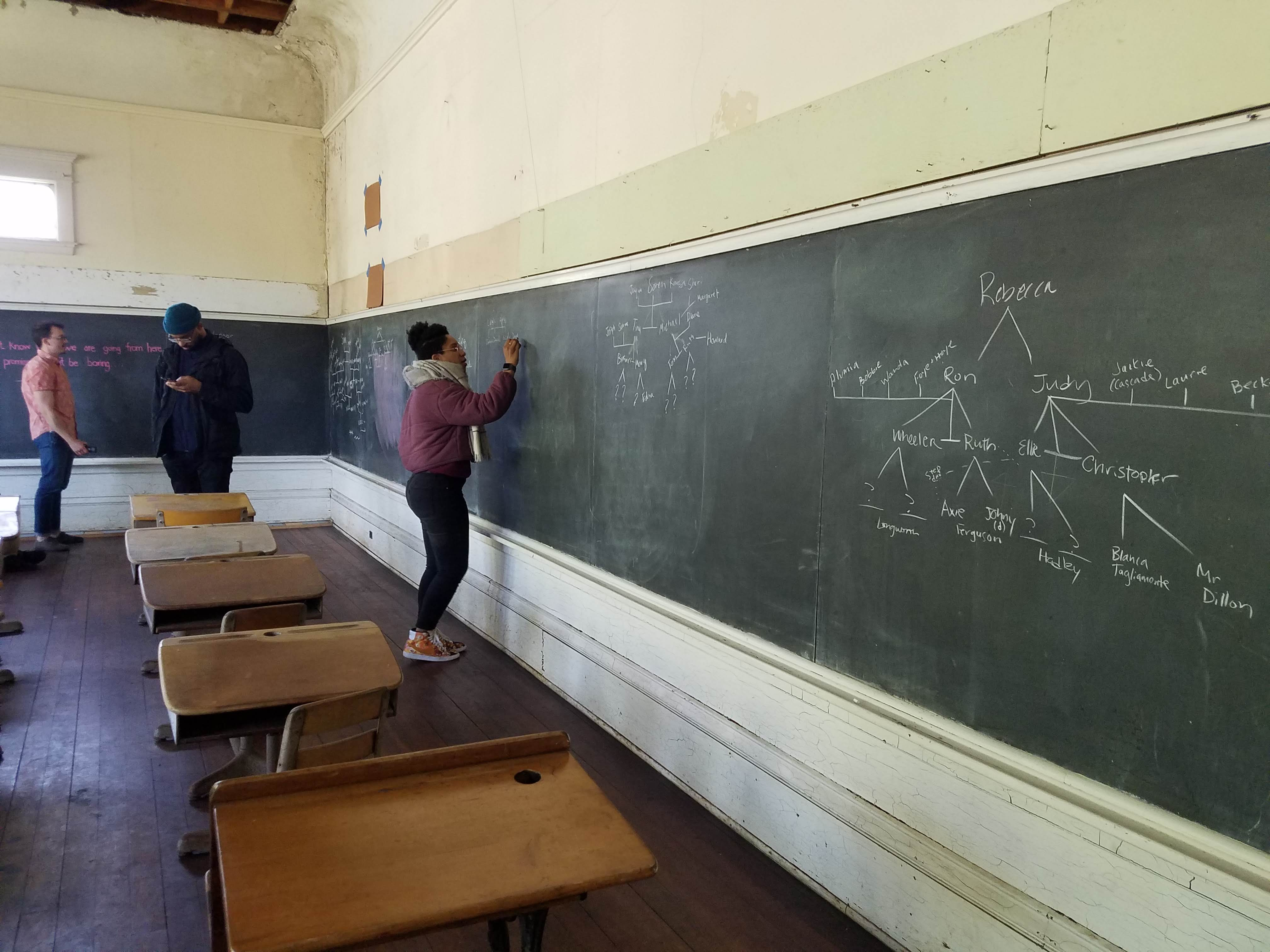 An actor stands near a row of old-fashioned school desks, writing on a long chalkboard