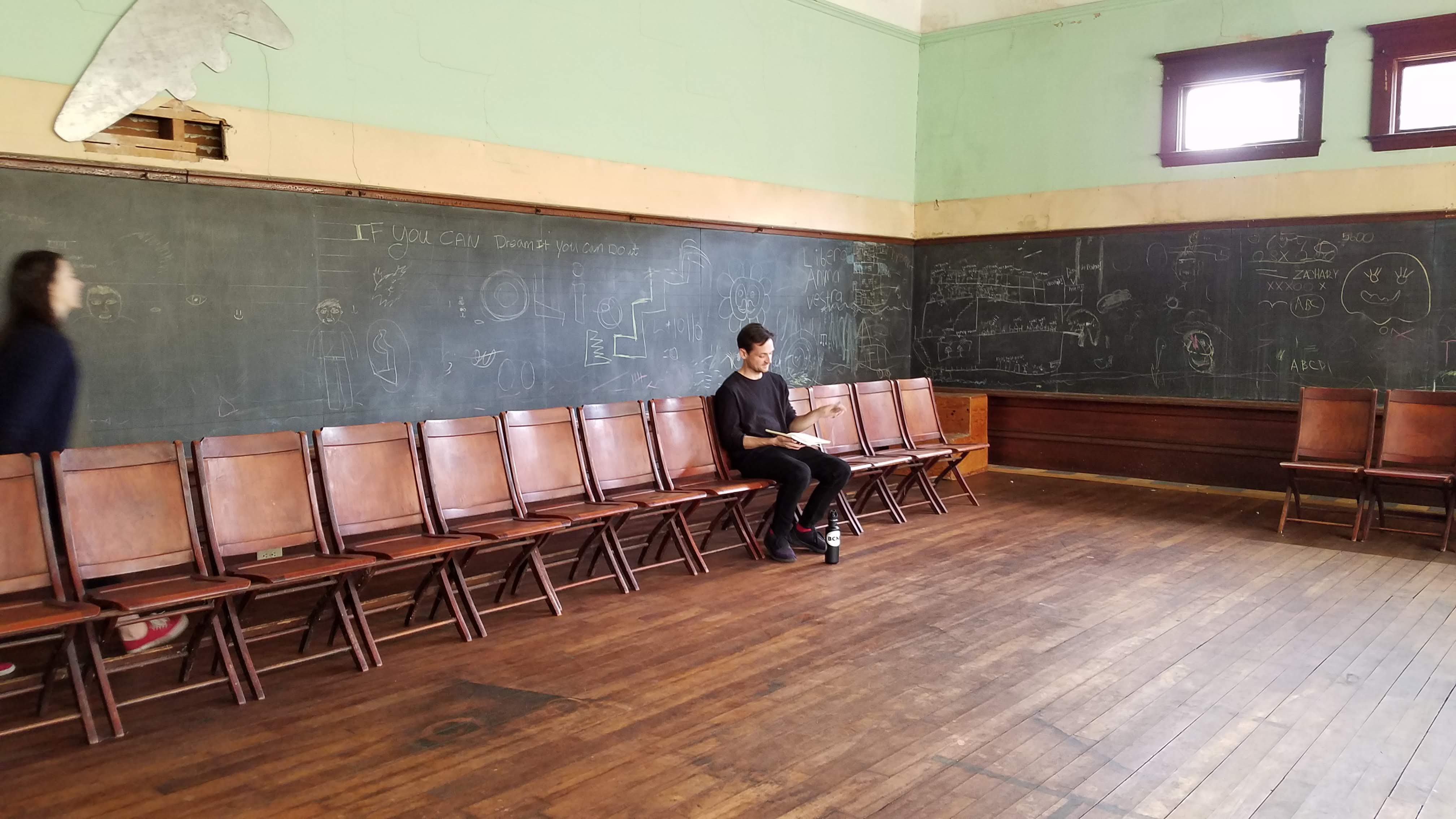 In an empty, antique schoolroom, one actor sits in a chair while another moves behind him.