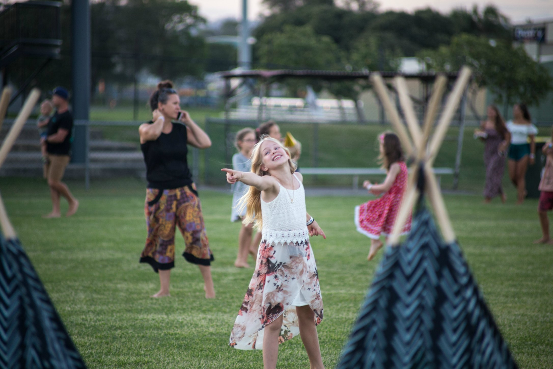 Girl pointing behind the teepees