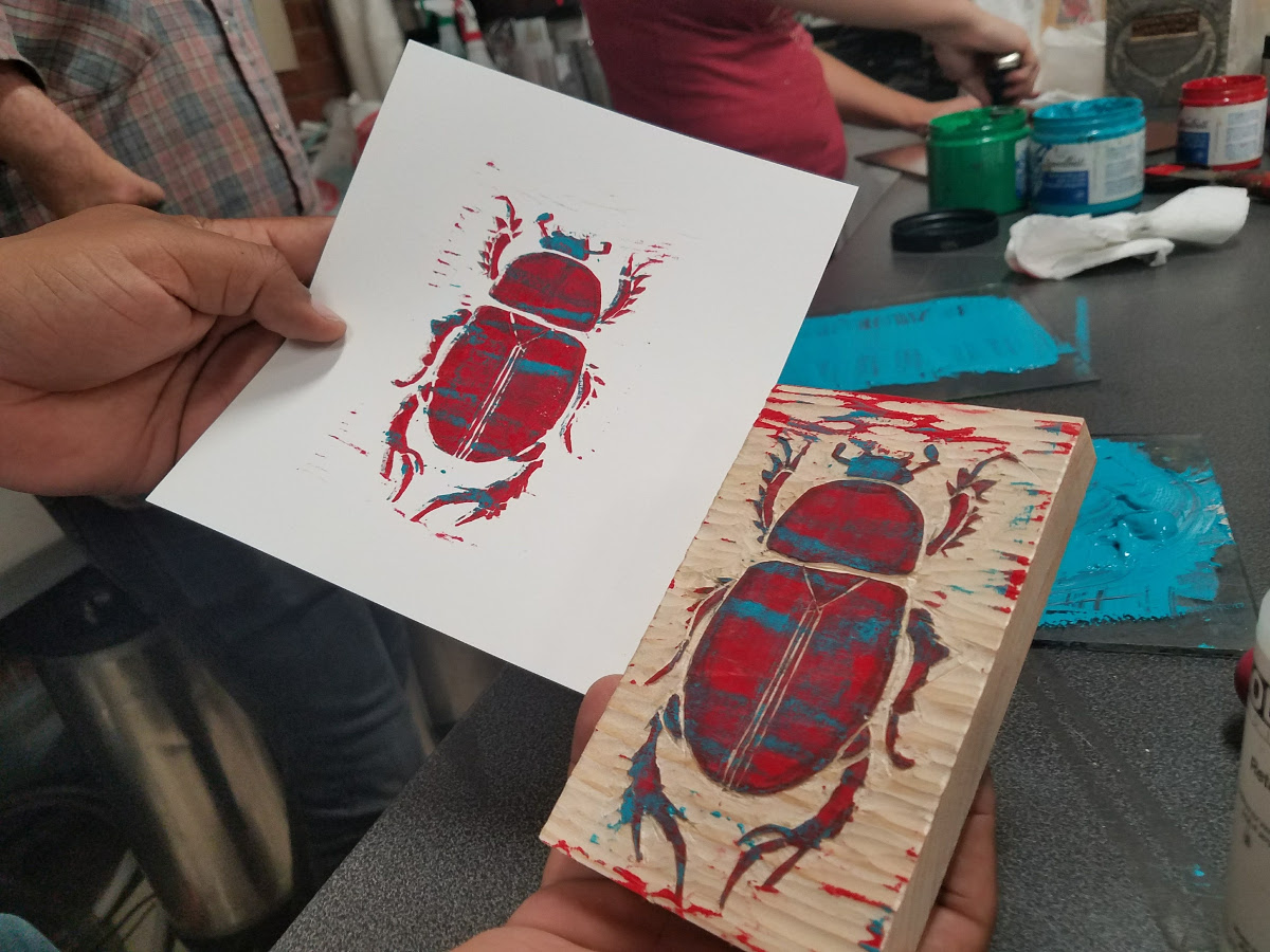 A woodcut printmaking student displays a finished print created using a woodblock made at MakeHaven in New Haven, CT.