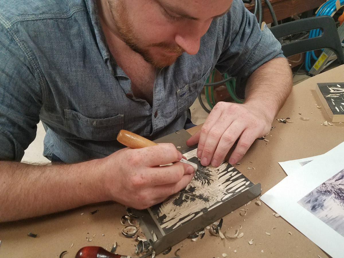 woodcut printmaking student carves a woodblock at MakeHaven in New Haven, CT.