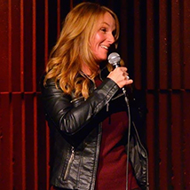 long blonde haired woman wearing black leather jacket, holding a mic in front of a red curtain on stage, head turned toward her right