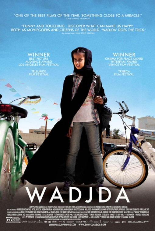 Young girl in Saudi Arabia stading in front of a green bike.