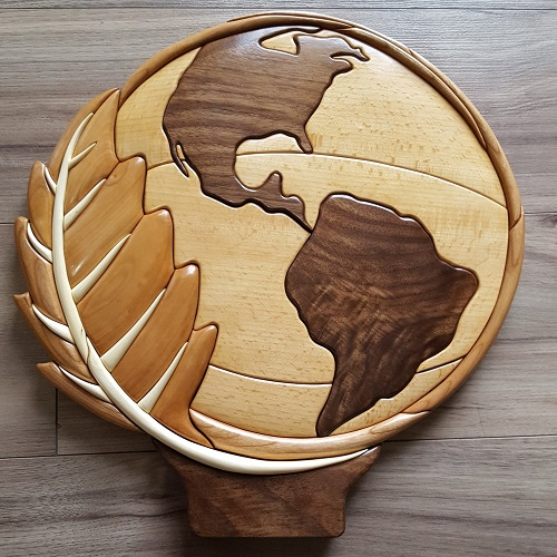 The Earth Ambassador Award is wood instarsia, made locally by a volunteer.