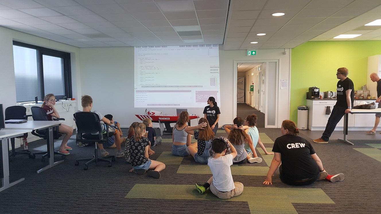 Kinderen luisteren aandachtig tijdens een workshop Sonic-Pi