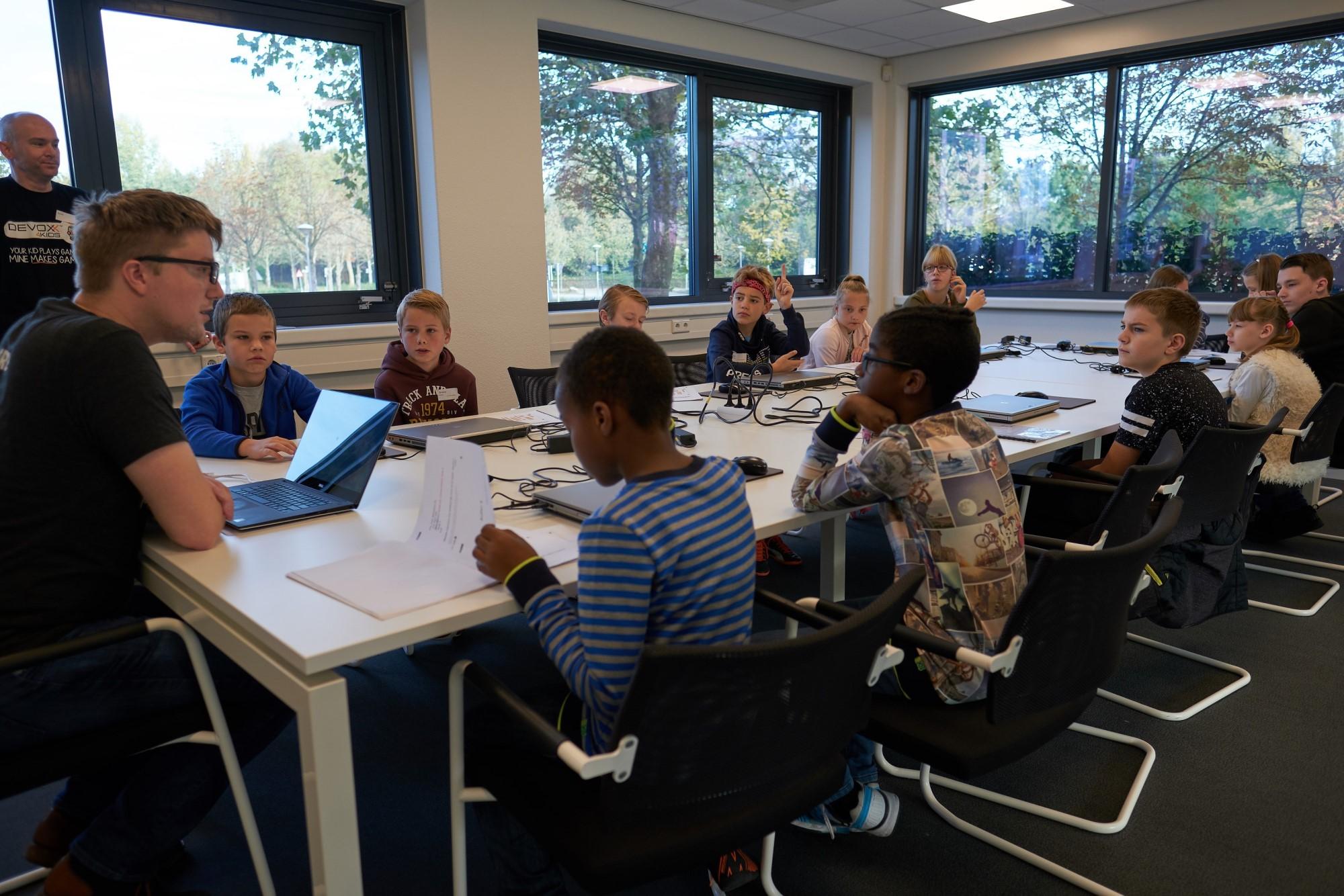 Kinderen luisteren aandachtig naar de uitleg van de workshop.