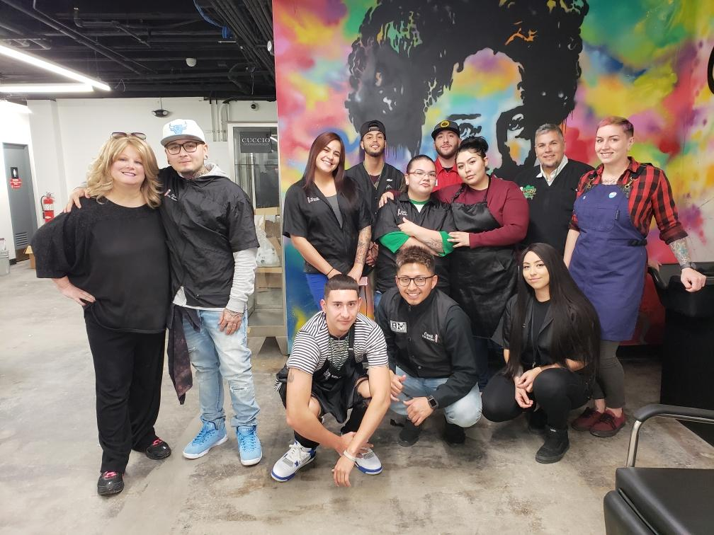 Students in front of the Emily Griffith mural in the new salon