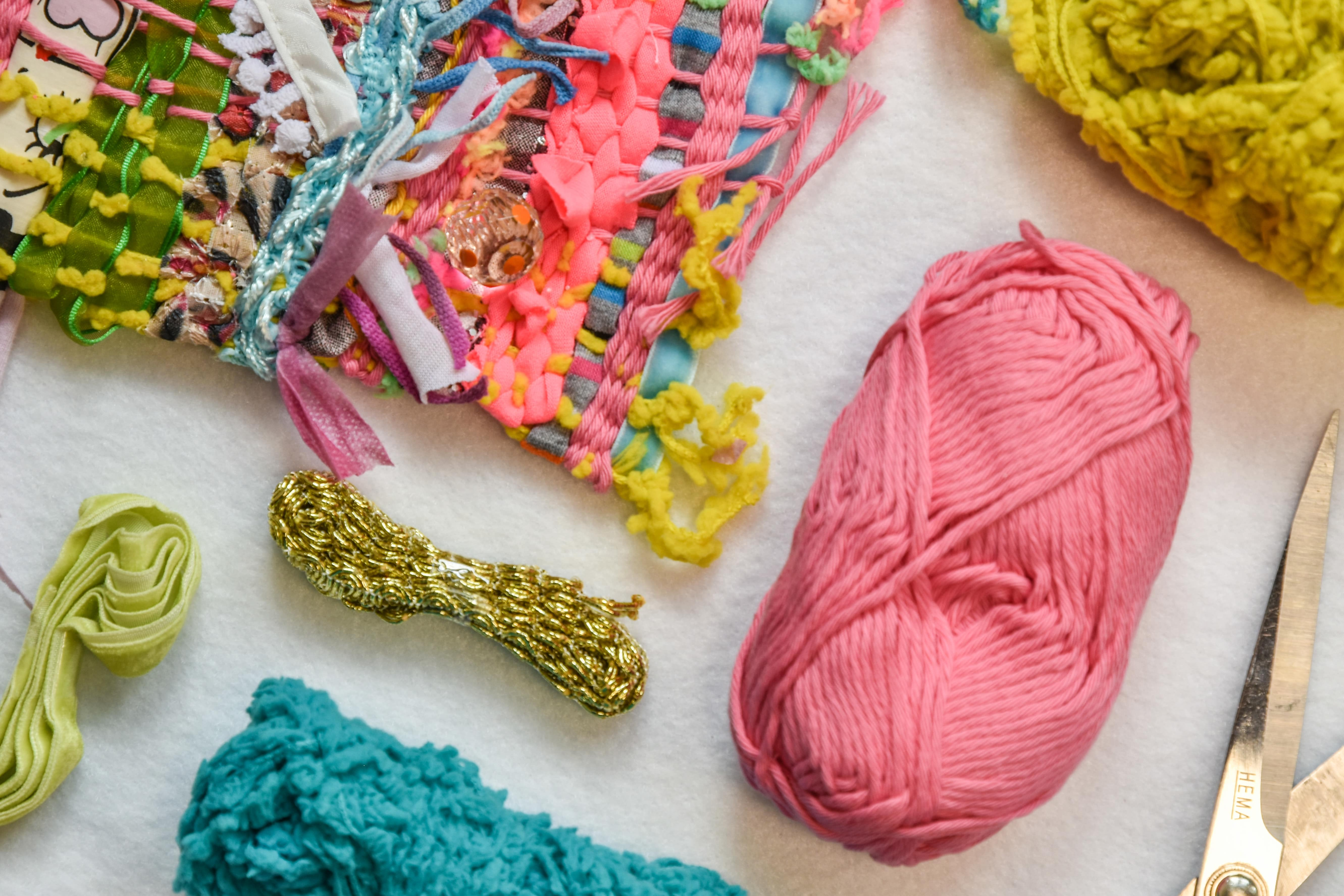 Stukje saori stijl weefsel en bolletjes felgekleurde draden in verschillende structuren en diktes