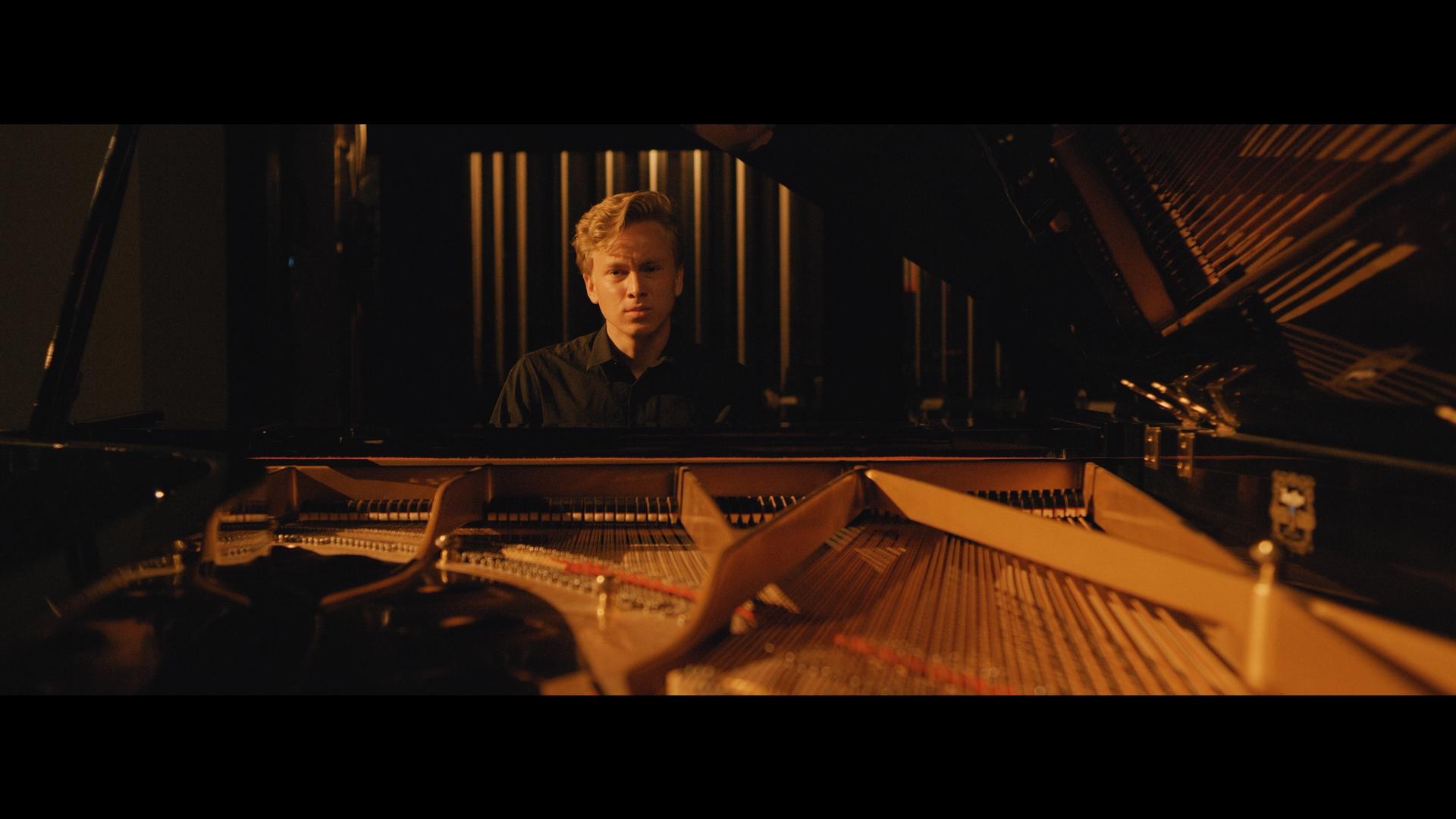 Nathan sits at a piano