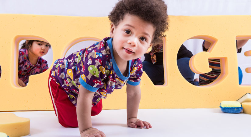 Toddler crawling in front of a pile of sponges