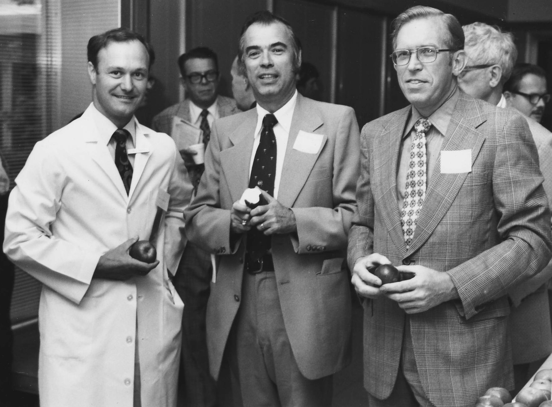 Dr. John Traubert (Center), enjoying his Hal Wanger apple with Dr. David Hunter (left) and Dr. William Wanger (Right) at the 2nd Annual Hal Wanger Family Medicine Conference