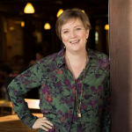 A photo of the webinar presenter - Heather Krause. Heather is leaning on a door, smiling, and wearing a green and purple floral top.