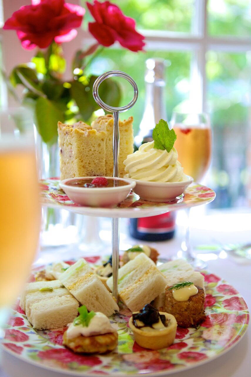 Glasses of champagne around a layered cake tray filled with treats. Background vase of flowers and sunlit window.