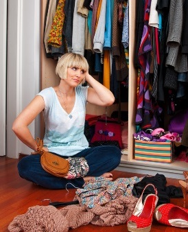 Picture of lady sitting on the floor beside her untidy wardrobe