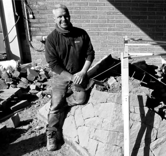 David Wilson smiling sitting on a stone wall he is constructing