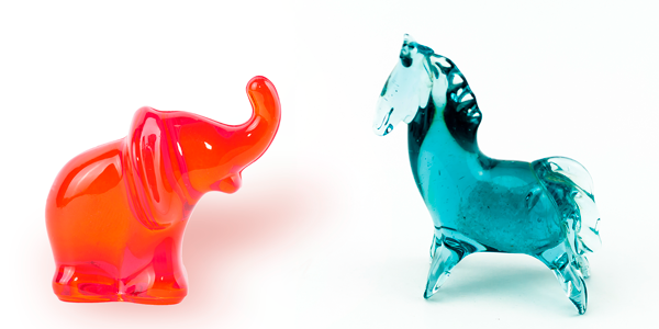 Image of a red elephant and a blue donkey, both made of blown glass