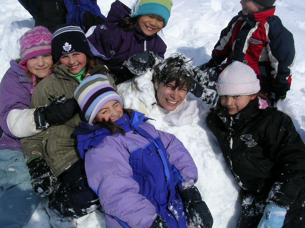 kids and counsellor playing in the snow