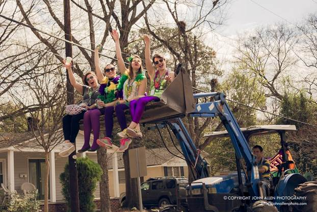 Revelers in Mardi Gras costumes in a tractor lift during Mardi Gras Columbia SC parade. Photo by John Allen