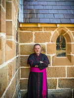 Father Rod Bower leaning against church wall