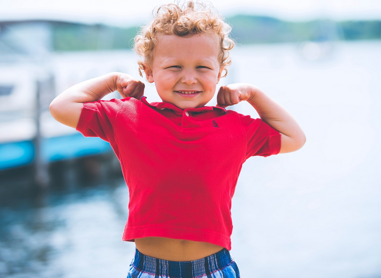 Little kid flexing his muscles