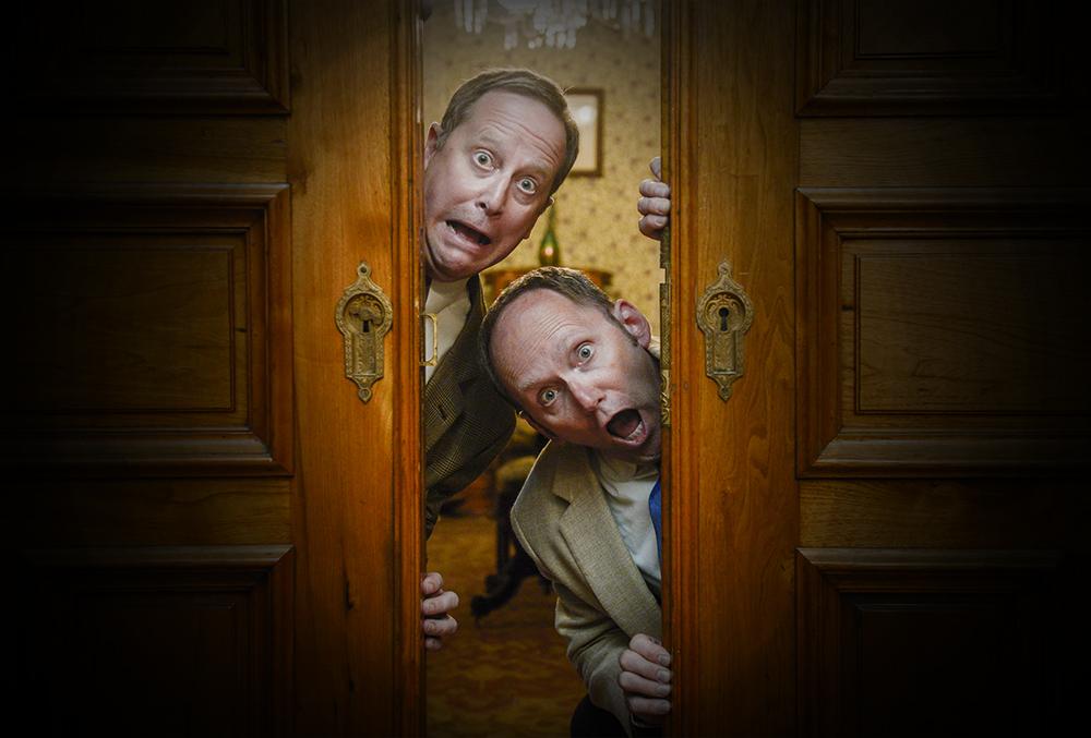 photograph of two surprised men peeking around a door.